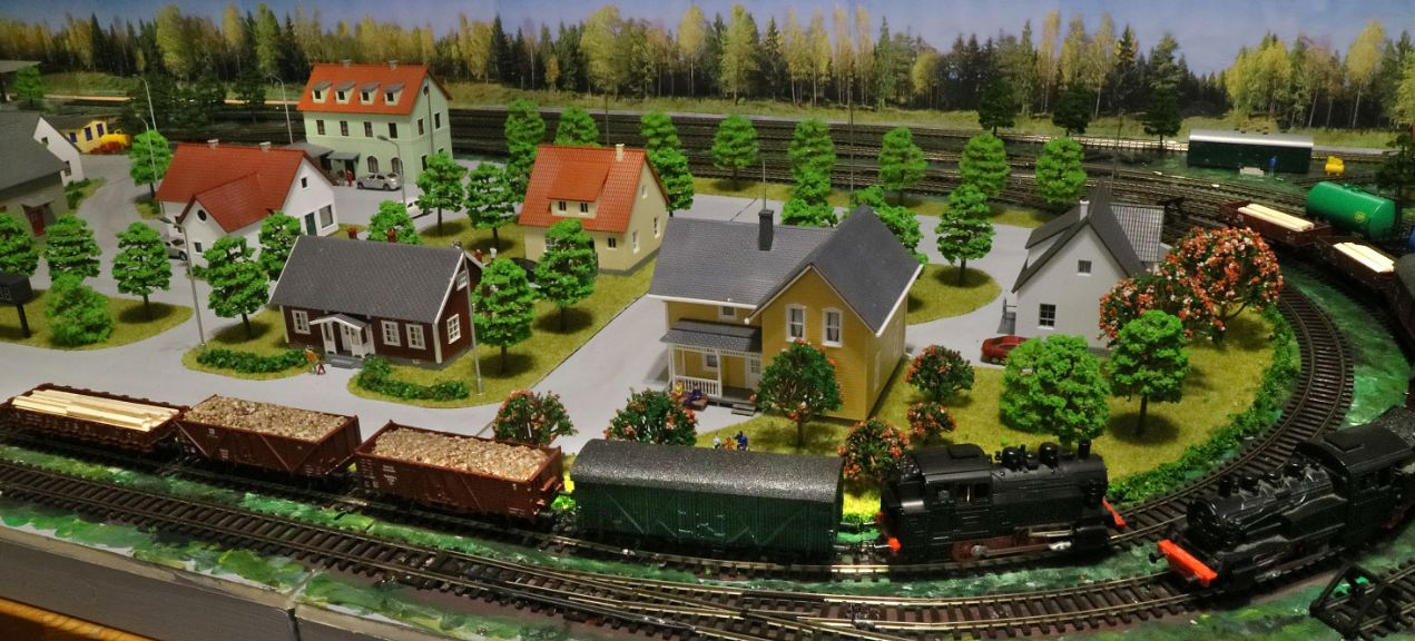 A relatively simple model train and track set, complete with miniature houses and landscapes.