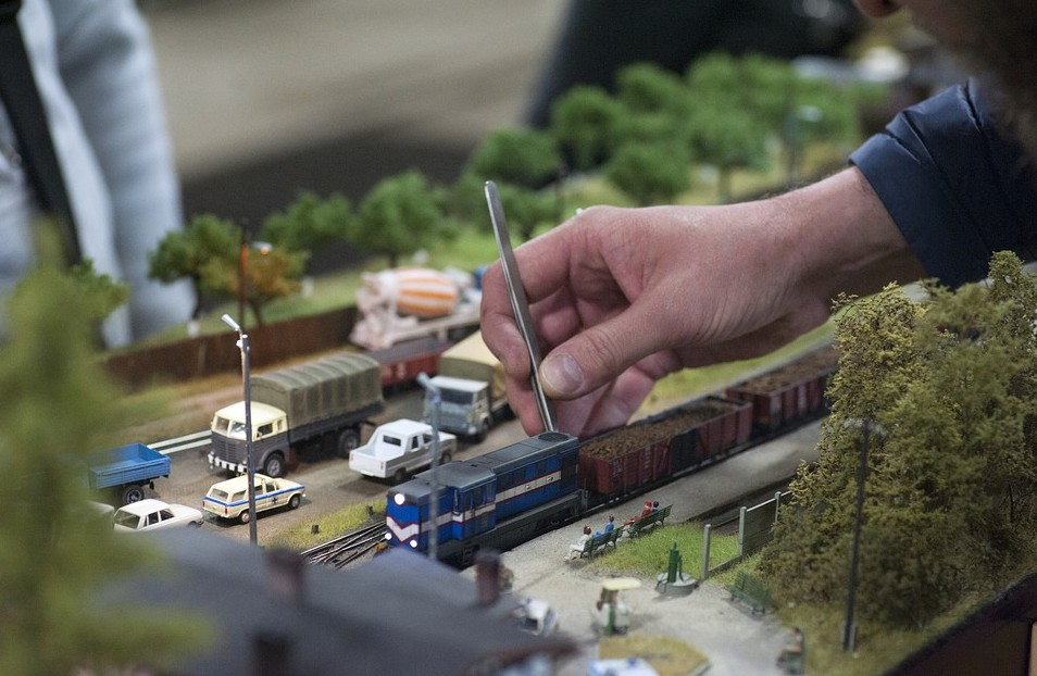 a person tinkering with train set