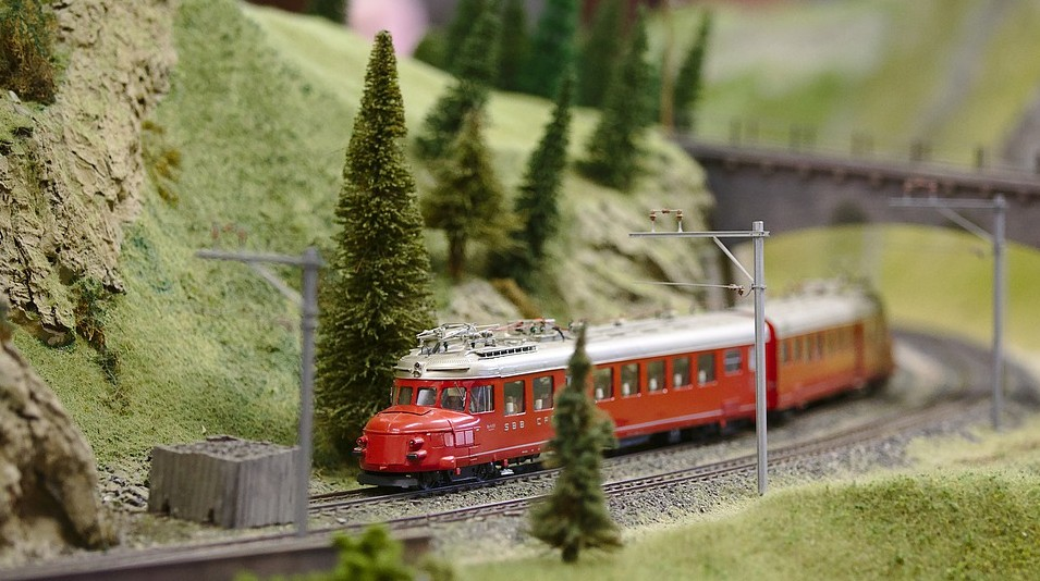 green mountains, red model train, tall pine trees, metal track