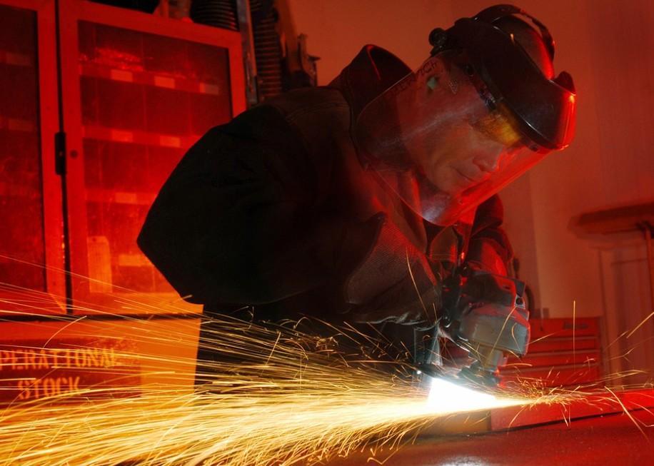 a man sanding metal, power tool, man wearing a safety helmet